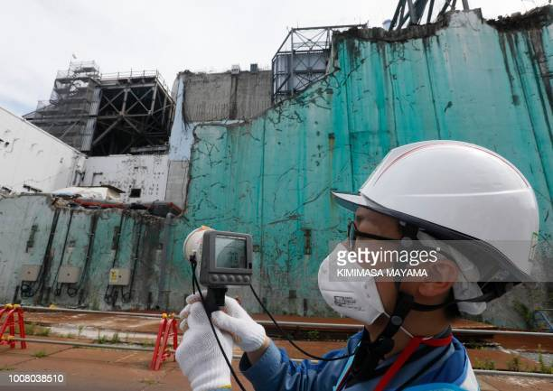 In this picture taken on July 27, 2018 and made available on July 30 a staff member of the Tokyo Electric Power Company measures radiation levels...