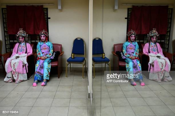 In this picture taken on July 28 2017 Chinese cantonese opera actresses Mia Zhai and Yujian Nuo from Beijing wait backstage before an opera...