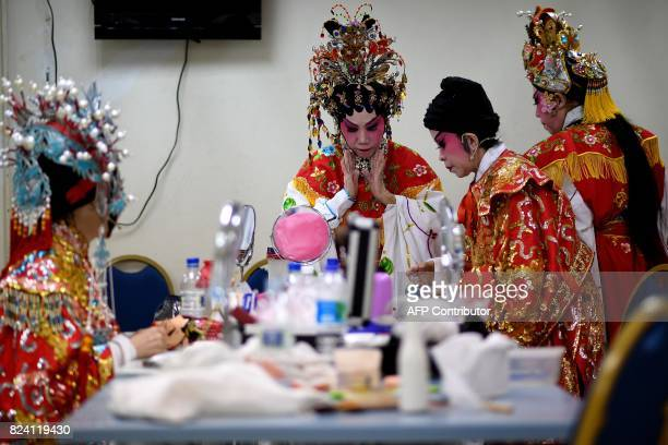 In this picture taken on July 28 2017 ethnic MalaysianChinese Cantonese opera artists from the Sound of Tai Hei group prepare backstage before an...