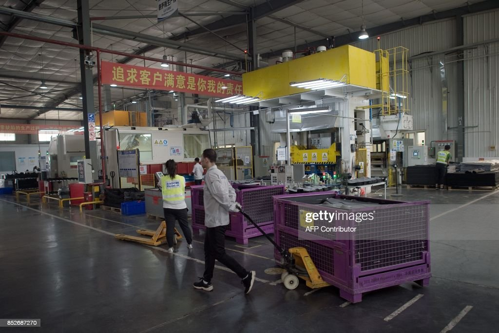 In this picture taken on July 3, 2017 a worker pulls a trolley containing car interior pieces for a major European car maker in the American Industrial Park in Shenyang. While foreign firms complain about being locked out of large swathes of China's vast market, the door has cracked open a bit wider in Liaoning province as the authorities seek to revive the recession-hit industrial region. CHIU
