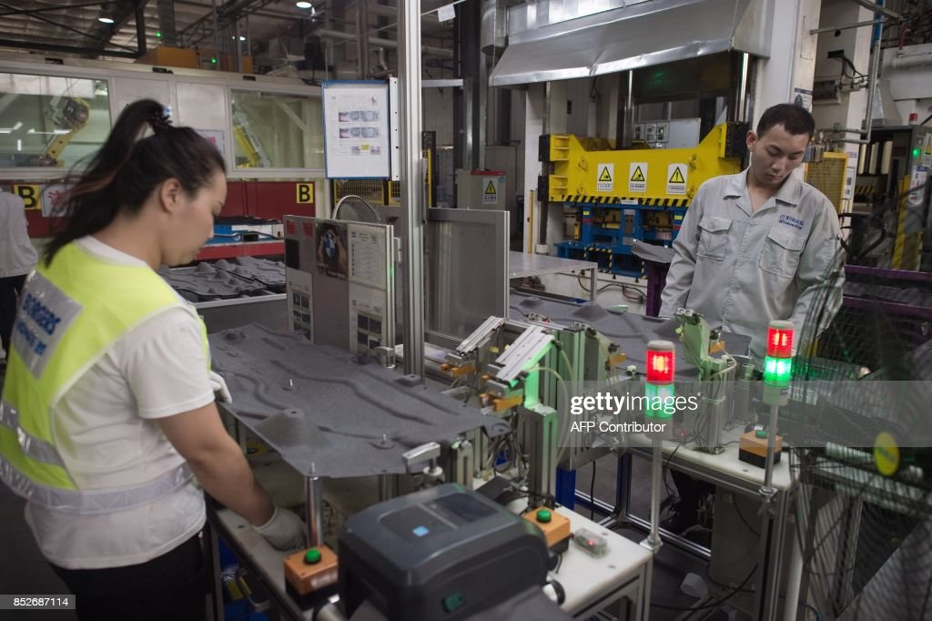 In this picture taken on July 3, 2017 workers manipulate a machine to make car interior pieces for a major European car maker in the American Industrial Park in Shenyang. While foreign firms complain about being locked out of large swathes of China's vast market, the door has cracked open a bit wider in Liaoning province as the authorities seek to revive the recession-hit industrial region. CHIU