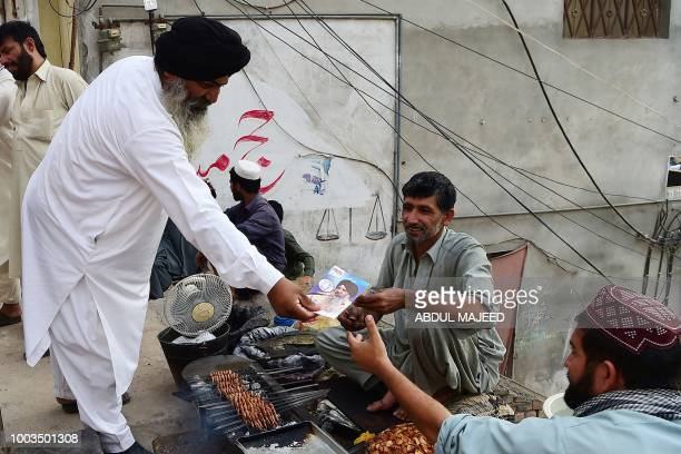In this picture taken on July 3 Radesh Singh Tony a minority Sikh candidate contesting an upcoming Pakistani general election seat distributes...
