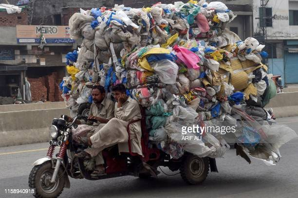 In this picture taken on July 31 men drive a threewheeler loaded with used plastic bags in Lahore From the once pristine rivers of Hindu Kush to the...