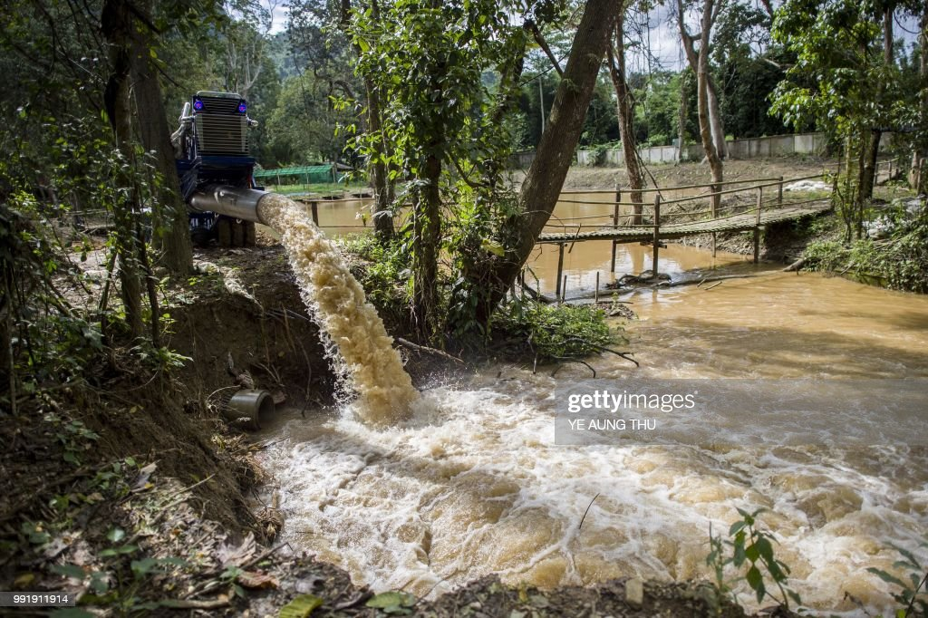 In this picture taken on July 4, 2018, water is pumped from Tham Luang cave during rescue operations for the trapped 12 boys and their coach, at Khun Nam Nang Non Forest Park in the Mae Sai district of Chiang Rai province. - Twelve boys and their football coach trapped in a flooded Thai cave for nine days were found alive late on July 3 after a painstaking search by specialist divers who finally discovered the emaciated group on a mud embankment. (Photo by YE AUNG THU / AFP) / To go with AFP story Thailand-cave-rescue-water-weather, Focus by Joe Freeman and Sippachai Kunnuwong