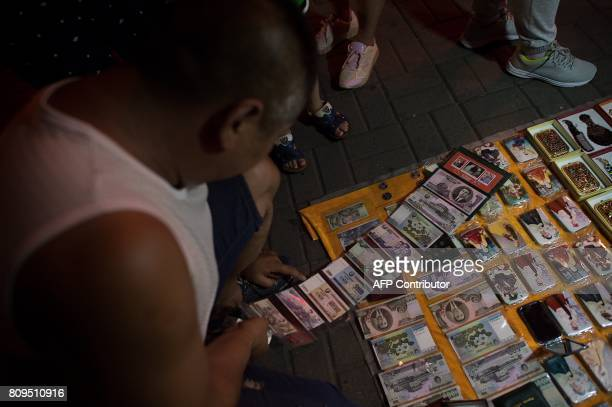 In this picture taken on July 5 2017 tourists are buying goods from North Korea on a street near the Friendship bridge on the Yalu River connecting...