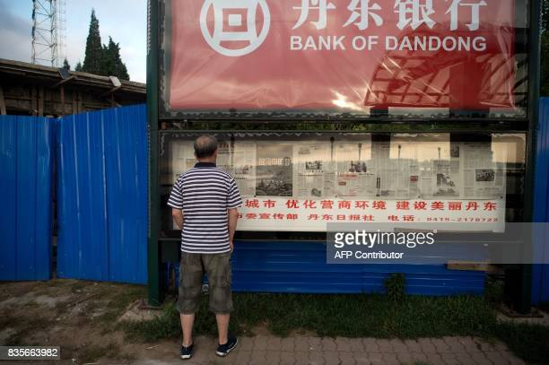 In this picture taken on July 5 a man reads a local newspaper on display below advertising for a bank in Dandong At the Chinese border with North...