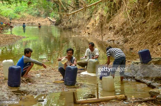 In this picture taken on July 5 villagers fill plastic jerry cans with water from the shrinking Cipamingkis river in Bekasi West Java province