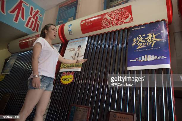In this picture taken on July 6 a vendor sells solar water heaters in a shop in Dandong At the Chinese border with North Korea solar panel traders...