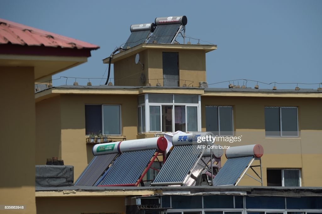 In this picture taken on July 6, 2017, solar water heaters are seen on the roof of a building in Dandong. At the Chinese border with North Korea, solar panel traders are shipping their products across the border by truck and boat, and greeting North Korean merchants in person at their stores in Chinas border city of Dandong. /