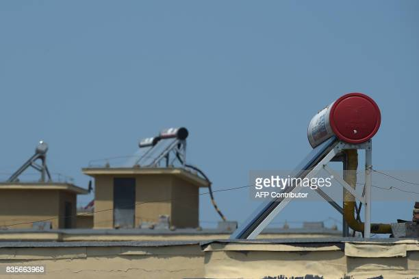 In this picture taken on July 6 solar water heaters are seen on the roof of a building in Dandong At the Chinese border with North Korea solar panel...
