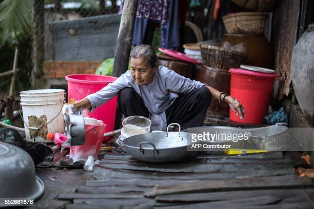 In this picture taken on July 7 83yearold Do Thi Duom washes dishes as other members of her family make rice paper at their home in Thuan Hung...