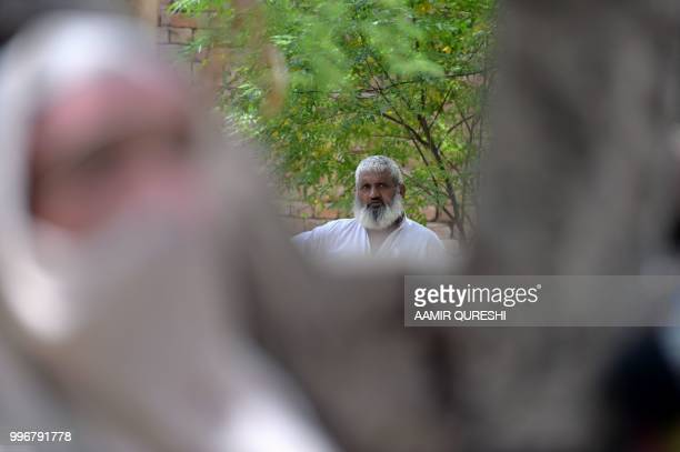 In this picture taken on July 7 a Pakistani man watches women chat in Mohri Pur village where women had previously been banned from voting some 60...