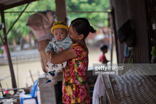 In this picture taken on July 7 Ha Thi Sau plays with her grandson at their home in Thuan Hung Village in the Mekong Delta after she stopped making...