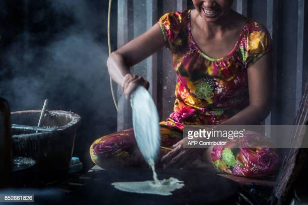 In this picture taken on July 7 Ha Thi Sau pours a rice and sesame mixture onto a hot fire stove as she and her daughter make rice paper at their...