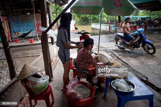 In this picture taken on July 7 Nguyen Thi Hue cooks rice paper over a makeshift charcoal stove as her daughter fixes her hair at the exit of a ferry...