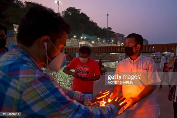 In this picture taken on June 11 a Hindu devotee takes blessings from holy fire after evening prayers at Har Ki Pauri ghat on the banks of river...