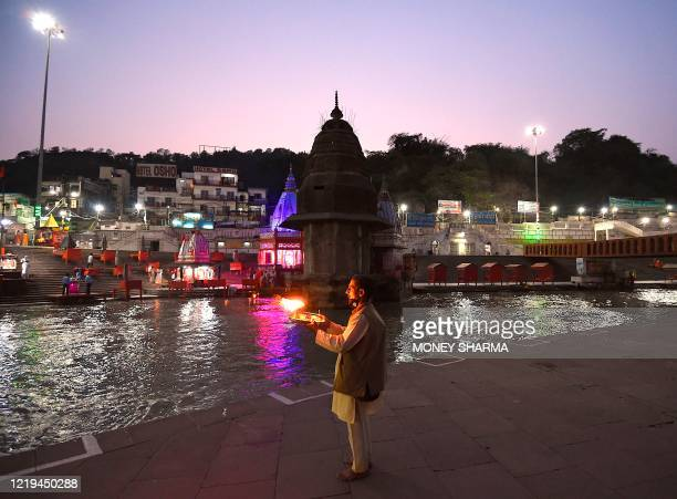 In this picture taken on June 11 a Hindu priest holds a plate after performing evening prayers at Har Ki Pauri ghat on the banks of river Ganges...