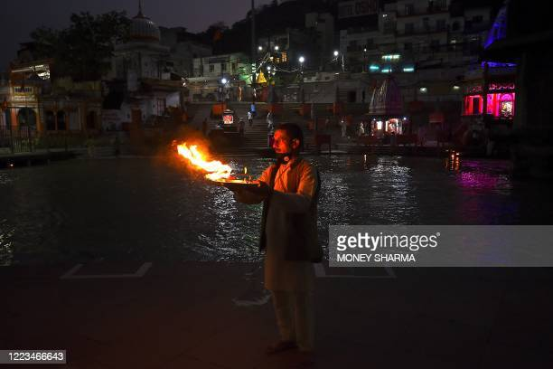 TOPSHOT In this picture taken on June 11 a Hindu priest holds a plate after performing evening prayers at Har Ki Pauri ghat on the banks of the river...
