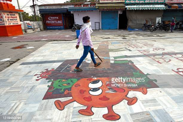 In this picture taken on June 11 a man walks over a coronavirus graffiti at Har Ki Pauri ghat on the banks of river Ganges after the government eased...
