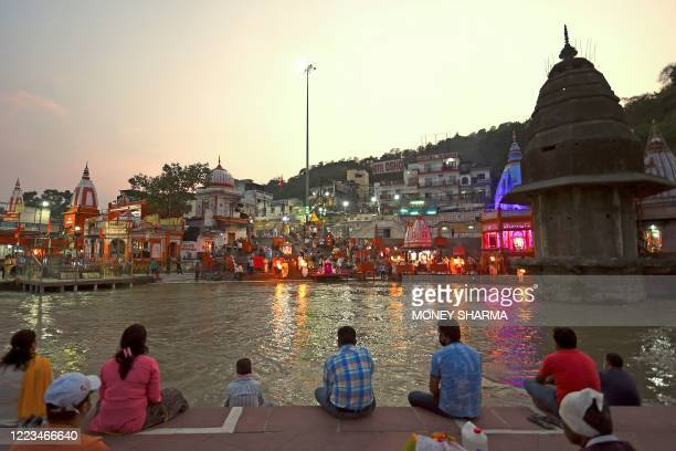 In this picture taken on June 11 Hindu devotees attend evening prayers at Har Ki Pauri ghat on the banks of the river Ganges after the government...