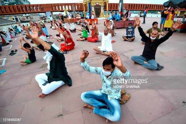 In this picture taken on June 11 Hindu devotees gesture as they attend evening prayers at Har Ki Pauri ghat on the banks of river Ganges after the...