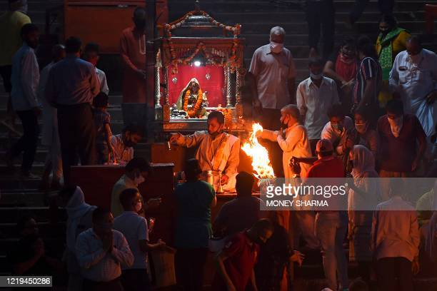 In this picture taken on June 11 Hindu devotees offer evening prayers at Har Ki Pauri ghat on the banks of river Ganges after the government eased a...