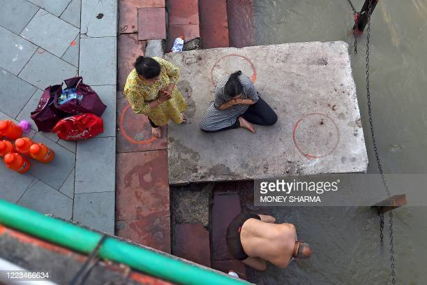 In this picture taken on June 11 Hindu devotees perform rituals at Har Ki Pauri ghat on the banks of the river Ganges after the government eased a...