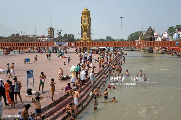 In this picture taken on June 11 Hindu devotees take a dip at Har Ki Pauri ghat on the banks of the river Ganges after the government eased a...
