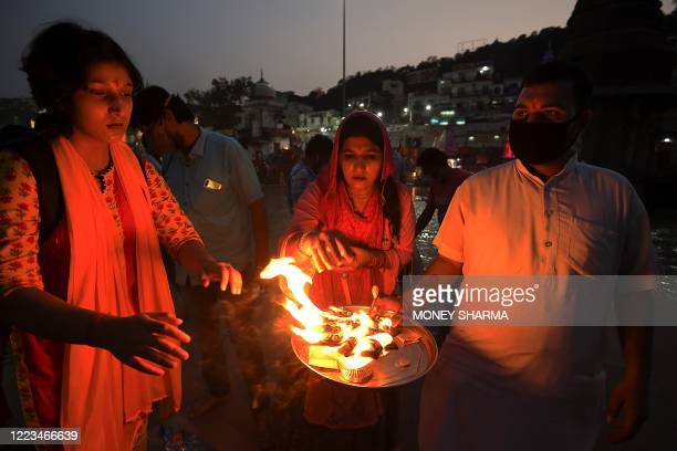 In this picture taken on June 11 Hindu devotees take blessings from fire after attending evening prayers at Har Ki Pauri Ghat on the banks of the...