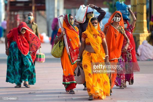 In this picture taken on June 11 Hindu devotees wearing facemasks arrive at Har Ki Pauri ghat on the banks of the river Ganges after the government...
