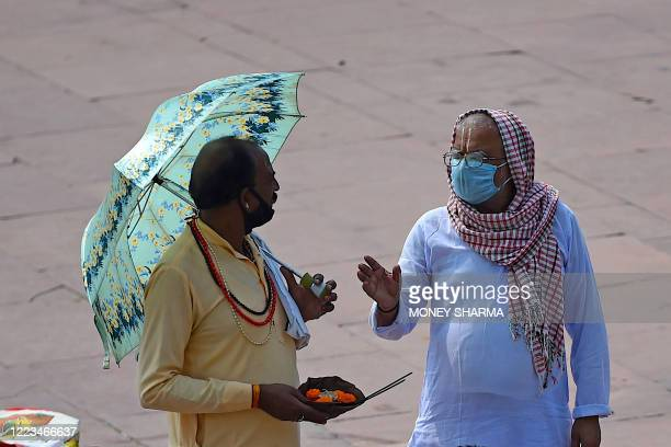 In this picture taken on June 11 Hindu priests talk at Har Ki Pauri Ghat on the banks of the river Ganges after the government eased a nationwide...