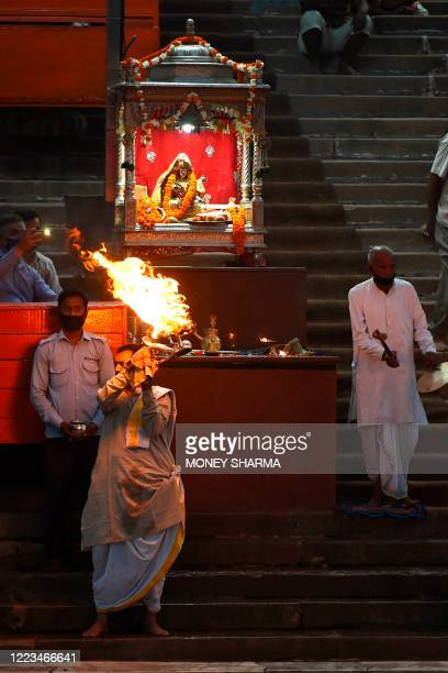 In this picture taken on June 11 priests perform evening prayers at Har Ki Pauri ghat on the banks of the river Ganges after the government eased a...