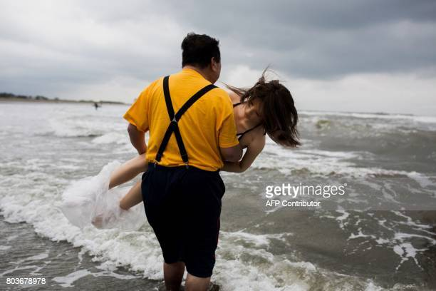 In this picture taken on June 14 62yearold Senji Nakajima carries his silicone sex doll Saori into the water to surf at Kujukuri beach Chiba...