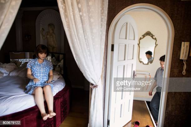In this picture taken on June 14 physiotherapist Masayuki Ozaki prepares to check out of a love hotel after spending a night with his silicone sex...