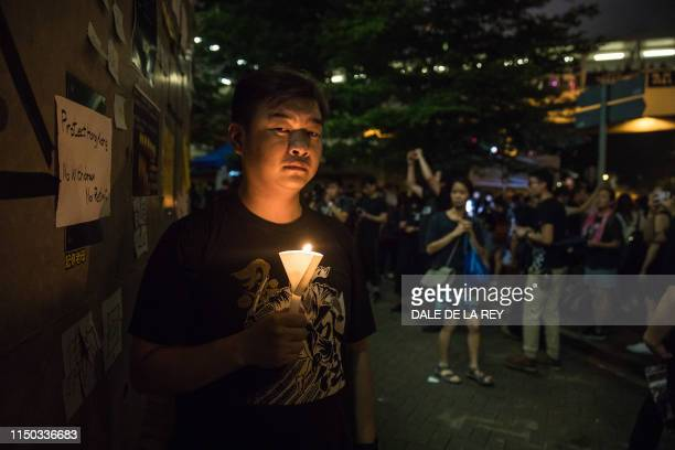 TOPSHOT In this picture taken on June 16 a protester holds a candle outside the government headquarters after a rally against a controversial...