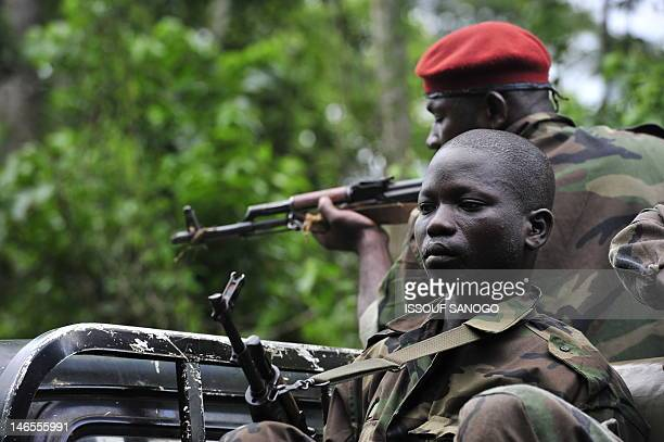 In this picture taken on June 17 2012 Ivory Coast soldiers patrol in the village of Para where UN soldiers were killed a week earlier following an...