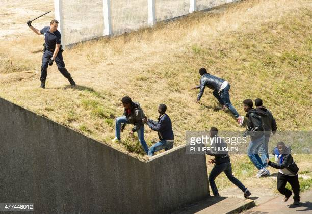 In this picture taken on June 17 2015 French antiriot police officer tries to prevent illegal migrants from hiding in trucks heading for England in...