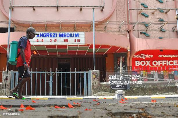 In this picture taken on June 18 a civic worker walks in front of a closed movie theatre complex due to a COVID-19 coronavirus lockdown in Mumbai. -...