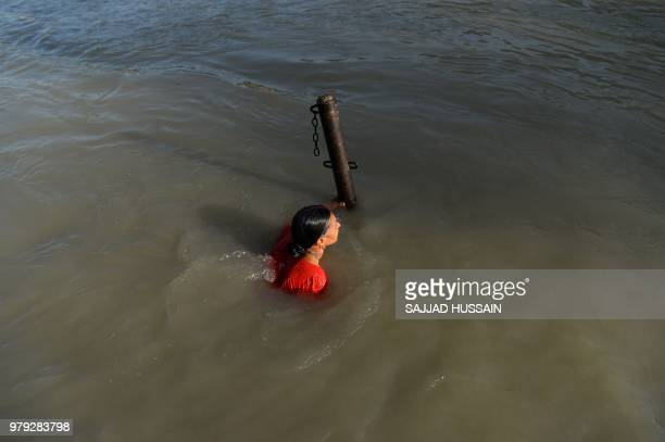 In this picture taken on June 18 a devotee takes a holy dip on the river Ganges in Rishikesh