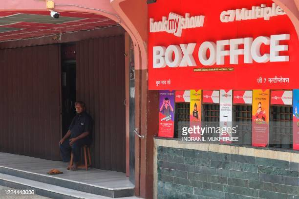 In this picture taken on June 18 a security guard sits at the entrance of a closed movie theatre complex due to a COVID-19 coronavirus lockdown in...