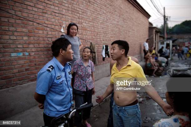 In this picture taken on June 20 a resident argues with a police officer as he tries to stop a group of residents from building a shower on a street...