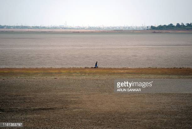 In this picture taken on June 20 an Indian youth walks on the dry banks of Puzhal reservoir on the outskirts of Chennai Indian residents carry a...