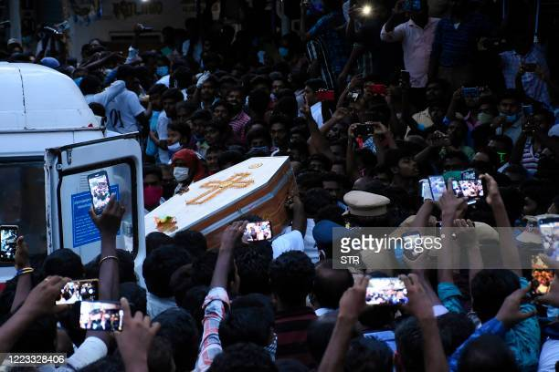 TOPSHOT In this picture taken on June 26 residents gather as they carry the coffin of Jayaraj and son Bennicks Immanuel allegedly tortured at the...