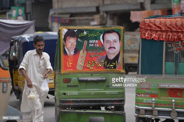 In this picture taken on June 28 a Pakistani pedestrian walks past a threewheeler auto rickshaw with a poster of a cricketerturned politician and...