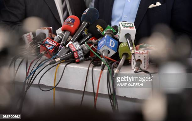 In this picture taken on June 28 microphones of the different Pakistani news channels are placed at a desk before a press conference outside the...