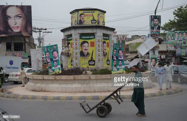 In this picture taken on June 28 Pakistani pedestrians make their way in front of posters of candidates taking part in the forthcoming general...