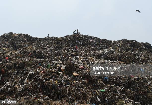 TOPSHOT In this picture taken on June 3 Indian rag pickers search for usable items at a landfill ahead of the 'World Environment Day' on the...