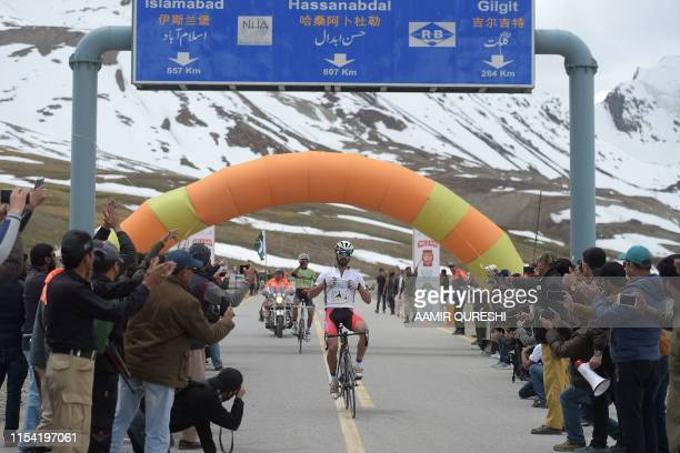 In this picture taken on June 30 Pakistani cyclist Najeeb Ullah celebrates as he crosses the finish line during the Tour de Khunjerab, one of the...