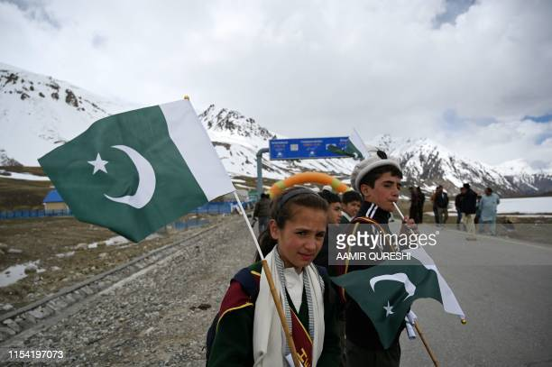 In this picture taken on June 30 Pakistani youths hold national flags as they cheer cyclists during the Tour de Khunjerab, one of the world's highest...