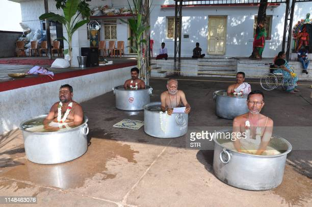In this picture taken on June 6 Hindu priests sit inside large vessels filled with water as they perform the 'Parjanya Japa' and offer prayers to...